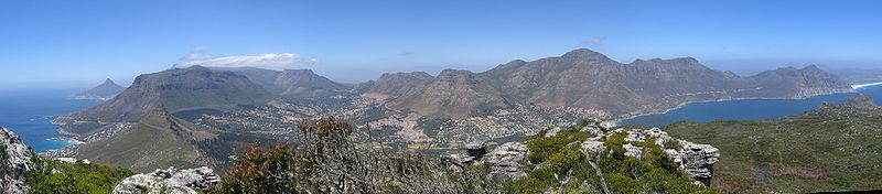 Image: Wikipedia Article/Public Domain/A panorama of Hout Bay, Cape Town, taken from Suther Peak, to the north-west of the village.